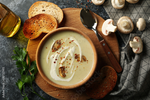 Tablou Canvas Concept of tasty lunch with bowl of mushroom soup on black smoky background