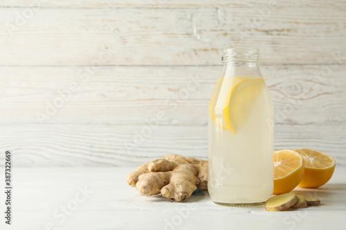 Bottle of ginger lemon water on white wooden background