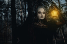 Portrait Of Woman In Image Of Witch With Glowing Lamp In Her Hand In Forest.