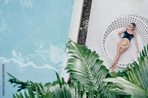 Obraz Enjoying suntan. Vacation concept. Top view of slim young woman in swimwear on the sun lounger near the swimming pool with palm trees. - fototapety do salonu