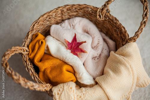 Fotografie, Obraz Wicker basket with linen. Knitted sweaters, maple leaf.
