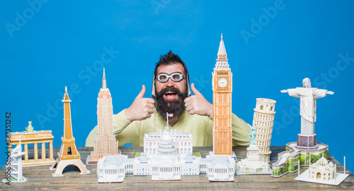 Obraz Traveling concept. Travel and vacation. Worlds monuments copy. 3d puzzles. Bearded man with 3d puzzles. Miniature buildings models. Man traveling. - fototapety do salonu