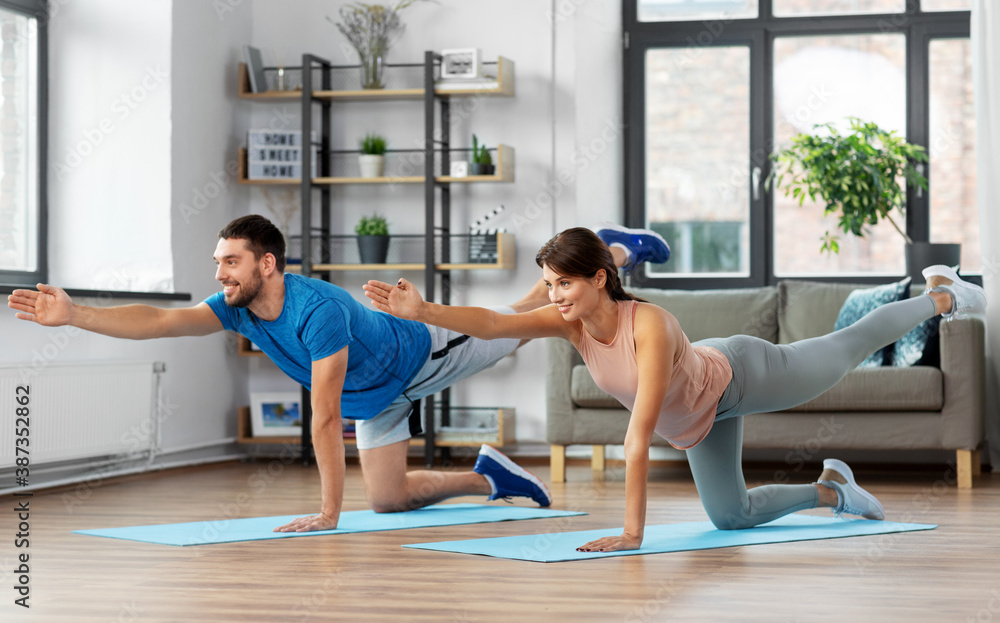Fototapeta sport, fitness, lifestyle and people concept - smiling man and woman exercising at home
