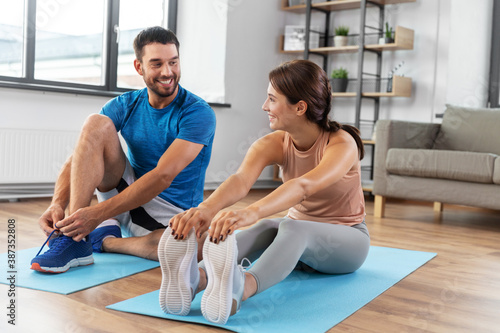 Foto sport, fitness, lifestyle and people concept - smiling man tying laces and woman
