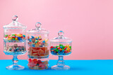 Fototapeta Kawa jest smaczna - Glass containers with candies against pink background