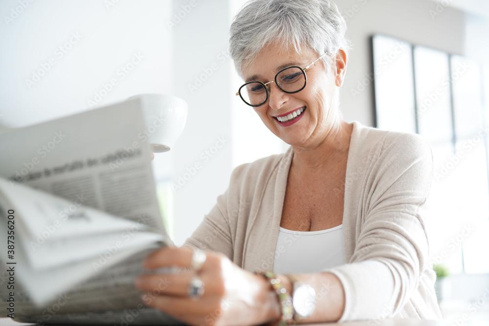 Fototapeta Portrait of smiling mature woman at home reading newspaper