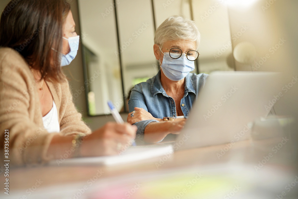 Fototapeta Business women working in office with face mask during 2019-ncov pandemia