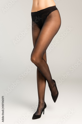 Obraz Cropped view of woman standing in black tights and shoes on grey - fototapety do salonu