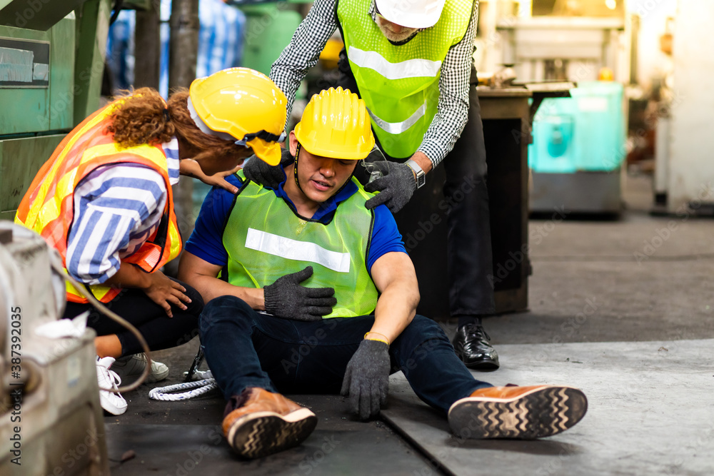 Fototapeta First Aid. Engineering supervisor talking on walkie talkie communication while his coworker lying unconscious at industrial factory. Professional engineering teamwork concept.