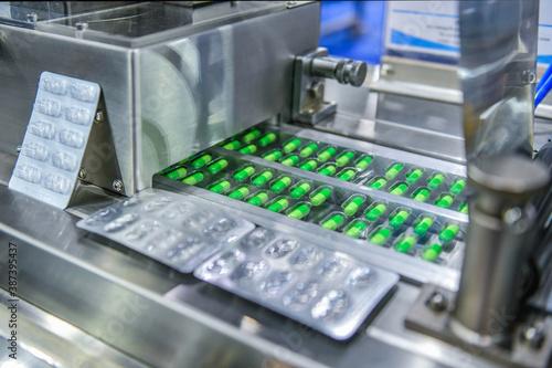 Obraz Green capsule medicine pill production line, Industrial pharmaceutical concept. - fototapety do salonu