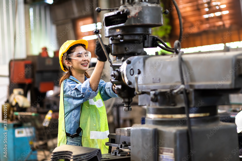 Fototapeta Woman worker wearing safety goggles control lathe machine to drill components. Metal lathe industrial manufacturing factory