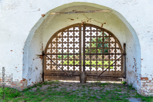 Ancient grid of closed gate in thick white brick wall of historical building near green grass in shadow on summer day Fototapet