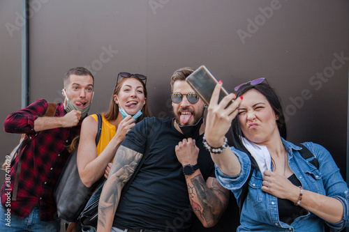 Slika na platnu group of reckless millennial friends taking a selfie while pulling down their fa
