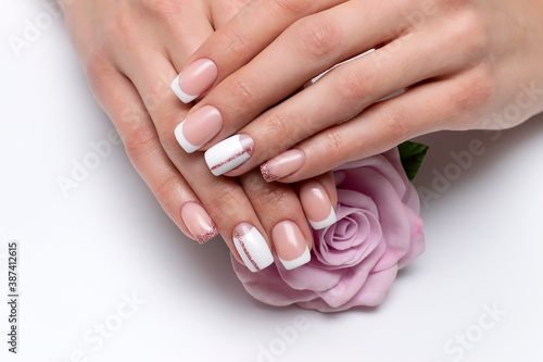 Valokuvatapetti French bridal white manicure with pink glittery stripe and shiny little finger on long square nails close-up on a white background holding a pink rose