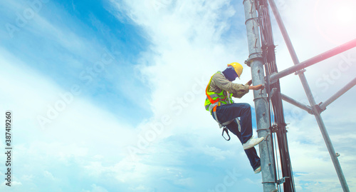 Fotografie, Obraz technician working on high telecommunication tower,worker wear Personal Protection Equipment for working high risk work,inspect and maintenance equipment on high tower