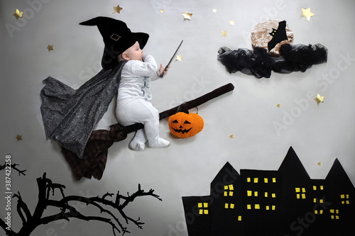 Fototapeta Halloween party baby on broom in wizard hat, magic wand flying to the moon with