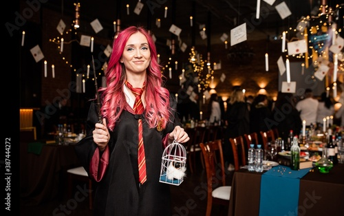 Fotografía A girl with pink hair in a Harry Potter-style suit with a magic wand in her hands stands in the appropriate magical interior and smiles