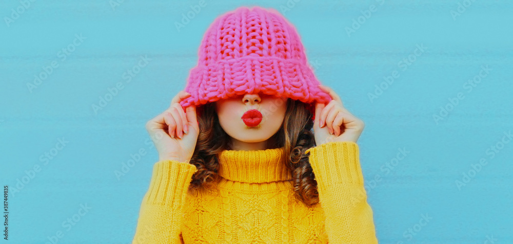 Fototapeta Winter portrait of young woman blowing red lips sending sweet air kiss female model wearing yellow knitted sweater on blue background