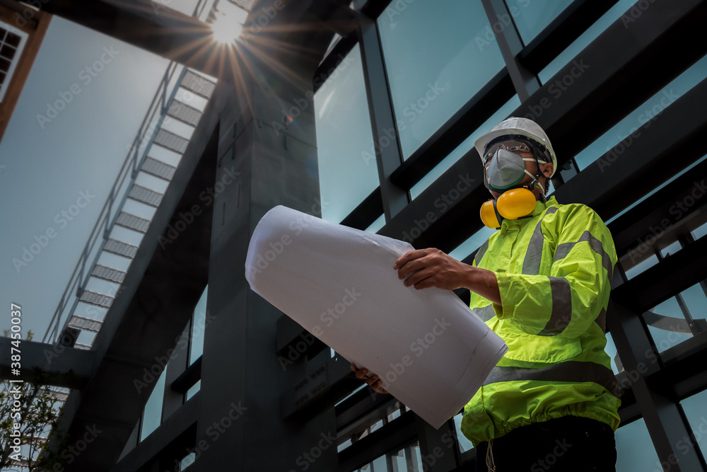 Fototapeta Civil Engineering people wearing face mask and safety helmet on construction site holding blueprint in his hand. Building inspector. Construction site check drawing and business workflow of building