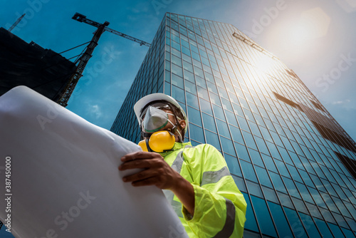 Leinwand Poster Civil Engineering people wearing face mask and safety helmet on construction site holding blueprint in his hand
