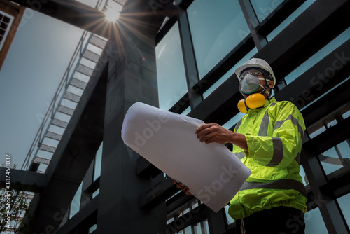 Vászonkép Civil Engineering people wearing face mask and safety helmet on construction site holding blueprint in his hand