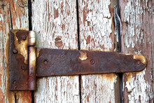 Rusty Metal Hinge On Old Wooden Door With A Peeled Blue Paint Abstract Background.