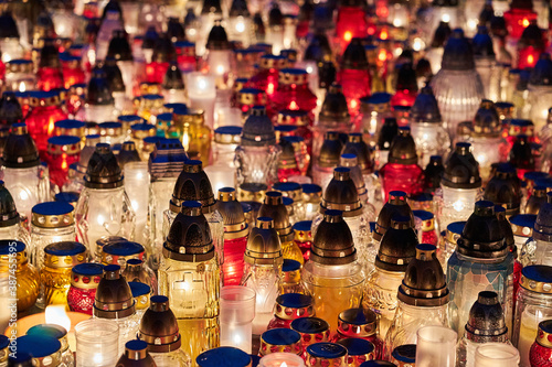 Fotografie, Obraz Candles burning on a grave in the cemetery of All Saints' Day