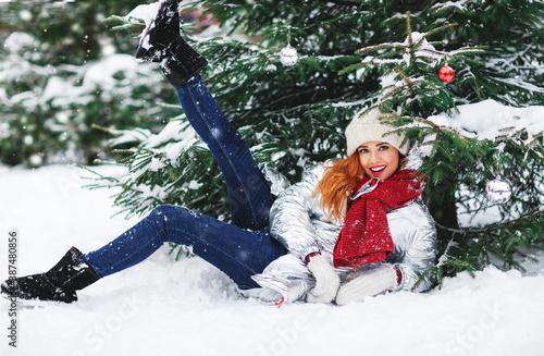 Slika na platnu Winter lifestyle portrait of pretty girl sitting on the snow ground under snowflakes falling down