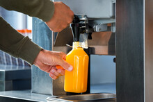 Man Fills A Plastic Bottle With Squeezed Orange Juice From A Juicer In Supermarket. Fresh Orange Juice In Hypermarket.