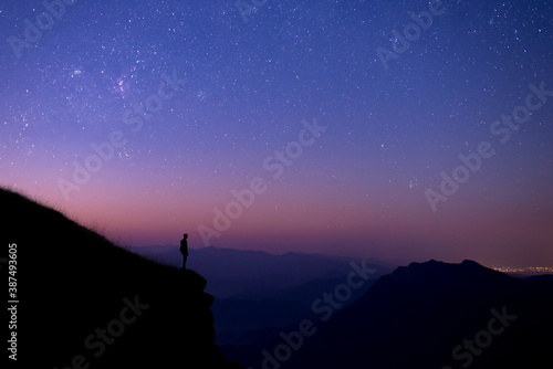 Silhouette of young tourists standing and watching the view of star and milky way and sunrise alone on the top of the mountain before sunrise. He is happy to be with herself and nature.