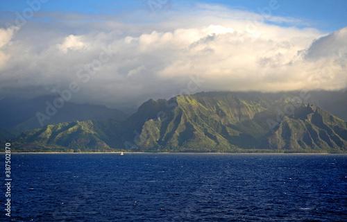 The Napali rugged coastline Hawaii, a small yacht is dwarfed by the dynamic rocky coast Fotobehang