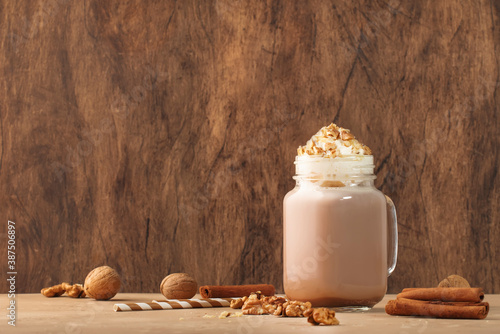 Obraz Winter hot dark chocolate or cocoa drink with whipped cream and crushed walnuts in glass jar, wooden table, copy space - fototapety do salonu
