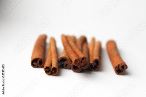 Fototapeta Loose cinnamon and cinnamon sticks on a white background