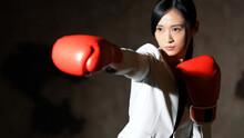 ボクシンググローブをつけてパンチするビジネスウーマン