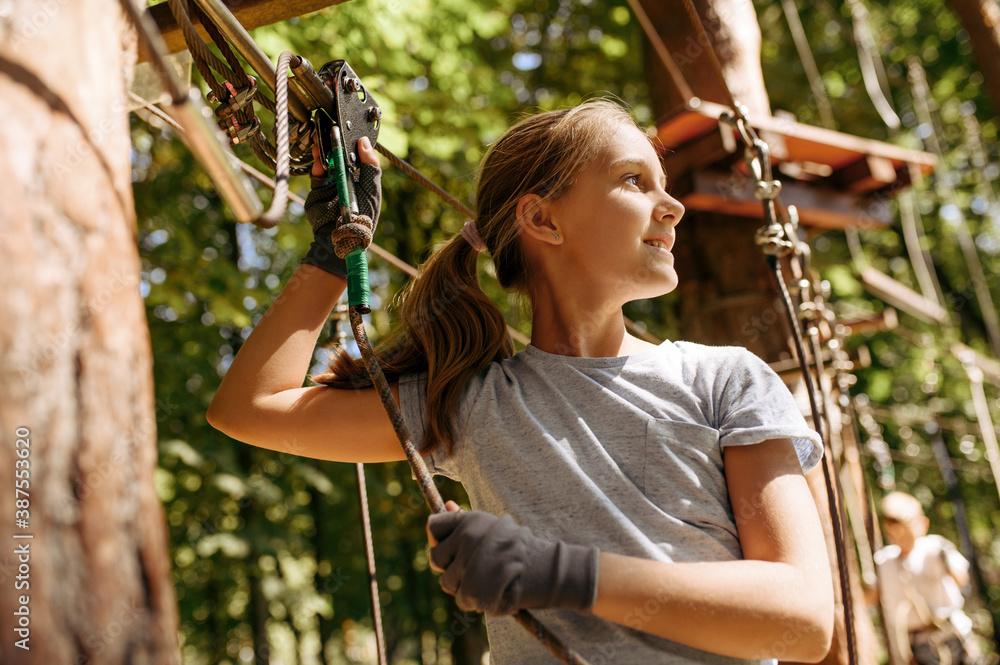 Fototapeta Little girl leisures in rope park, playground