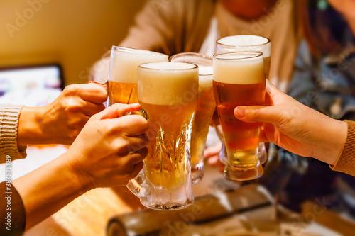 Valokuva 居酒屋で乾杯する大勢の人の手とジョッキビール