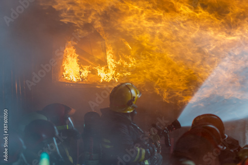 Firefighters battled the raging fire with large flames that burned down residential buildings Fototapeta