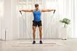 Leinwandbild Motiv Full length hot of a muscular guy exercising with a resistance band at home