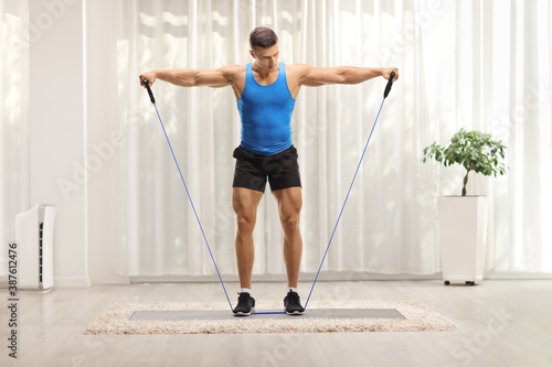 Obraz Full length hot of a muscular guy exercising with a resistance band at home - fototapety do salonu