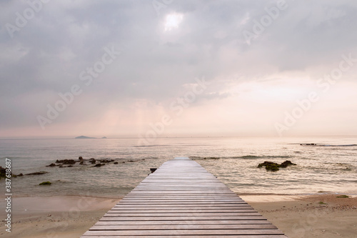 Wood bridge on the sea which has walk way for travel tourism and beautiful sky with sunshine in the morning Fotobehang