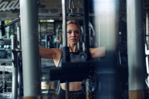 Fotografia Young fitness woman execute exercise with exercise-machine in gym