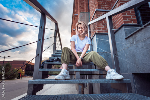 Obraz na plátně Girl in hip hop clothes sitting on a metal staircase looking at camera with a re