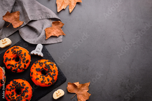 Vászonkép Pumpkin and chocolate donuts, spooky ghosts marshmallows and dried leaves on gre