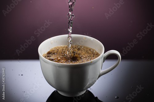 Fototapeta Making instant freeze-dried coffee in a white mug with reflection on a gradient