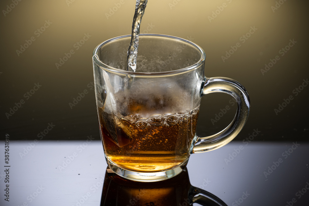 Fototapeta Brew black tea from a sausage bag in a transparent mug with reflection on a gradient background