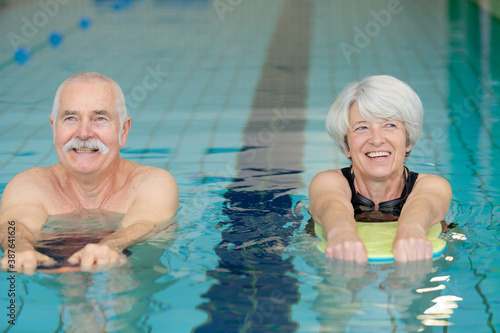 senior couple exercising with floats in swimming pool