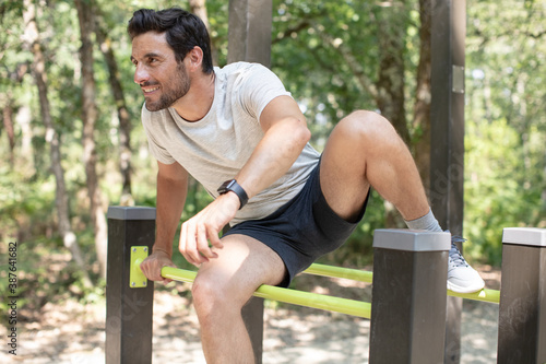 Obraz fit man doing exercises in forest outdoor gym using bars - fototapety do salonu