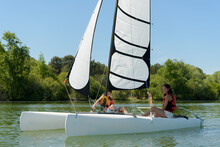 A Couple Is Sailing A Sailboat