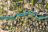 Aerial pass over Kibbutz Nir David with Asi river channel turquoise water dividing east and west side riverside houses and palm trees, Israel.