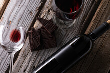 Close-up Top View Of Elegant Bottle And Wineglasses With Red Wine And Dark Chocolate On Rustic Wooden Background. Wine And Dessert. Template Concept For Your Design And Advertising Company Promotion